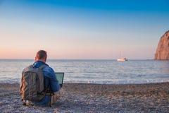 Junger Mann mit Laptopfunktion auf dem Strand Freiheit, Fernarbeits-, Freiberufler-, Technologie-, Internet-, Reise- und Ferienko lizenzfreie stockfotografie