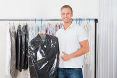 Junger Mann mit Mantel in der Chemischen Reinigung stockfotos