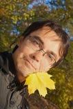Junger Mann mit maplel Blatt in seinem Mund Stockfotos