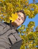 Junger Mann mit maplel Blatt in seinem Mund Lizenzfreie Stockfotografie