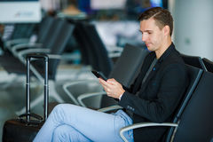 Junger Mann mit Mobiltelefon nach innen im Flughafen Junger Mann mit Smartphone am Flughafen beim Warten auf das Verschalen Lizenzfreie Stockfotografie