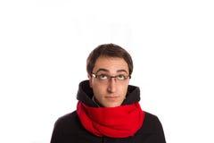 Junger Mann mit Montgomery und rotem Schal schaut oben, an lokalisiert Lizenzfreies Stockfoto