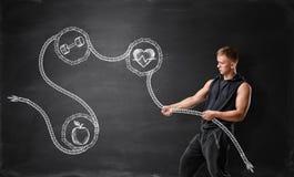 Junger Mann mit Muskeln, der gezeichnetes Seil mit Apfel, Dummkopf zieht und Herz schlägt lizenzfreie stockfotografie
