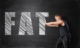 Junger Mann mit Muskeln, der großes gezeichnetes fettes Wort durch beide Hände auf dem Hintergrund einer Tafel drückt stockbild