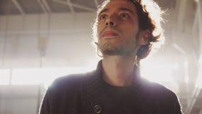 Junger Mann mit Ohrenpfropfen geht entlang Betriebszeitlupe stock video