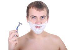 Junger Mann mit Rasiermesser und rasierenschaumgummi Lizenzfreies Stockbild