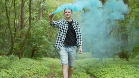 Junger Mann mit Rauchbombe gehend in Wald stock footage
