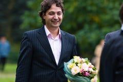 Junger Mann mit schönem Blumenstrauß der Blumen Stockfoto
