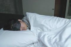 Junger Mann mit Schlafenmaskenschlaf auf dem Bett Stockfoto