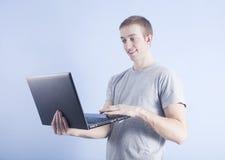 Junger Mann mit schwarzem Laptop auf blauem Hintergrund stockfotos