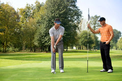 Junger Mann mit seinem Freund, der Golf im Golfplatz spielt Lizenzfreie Stockbilder