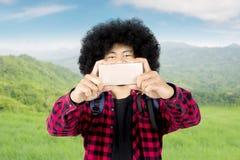 Junger Mann mit Smartphone in der Wiese Stockfotografie