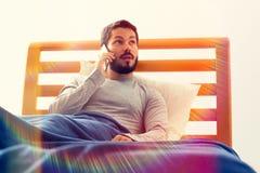Junger Mann mit Smartphone in einem Anruf Lizenzfreies Stockfoto