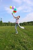 Junger Mann mit Springen vieler dem farbigem Ballone Lizenzfreie Stockfotos