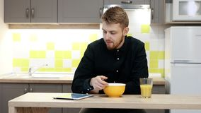 Junger Mann mit Tablette das Frühstück essend, das zu Hause durch Tabelle in der Küche sitzt stock footage