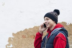 Junger Mann mit Telefon auf altem Wandhintergrund Lizenzfreies Stockbild