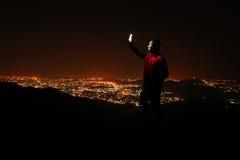 Junger Mann mit Telefon auf den Hügel, die Nachtstadtansicht beobachtend Stockfotografie