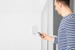 Junger Mann mit Telefon nahe Sicherheitssystem zuhause lizenzfreies stockbild