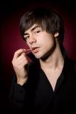 Junger Mann mit Toothpick im schwarzen Hemd stockfoto