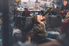 Junger Mann mit trinkendem Bier des Katers von der Flasche im unordentlichen Raum nach Partei Lizenzfreies Stockfoto