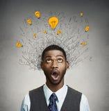 Junger Mann mit vielen Glühlampen der Idee über dem Kopf, der oben schaut stockfotos
