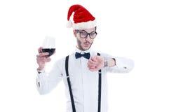 Junger Mann mit Weihnachtshut betrachtet seine Uhr Lizenzfreie Stockbilder