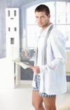 Junger Mann mit Zeitung und Tee morgens Lizenzfreies Stockfoto