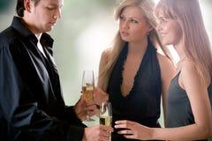 Junger Mann mit zwei Gläsern mit der Stellung des Champagners und zwei Frauen Lizenzfreies Stockbild