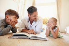 Junger Mann mit zwei Kindern, die eine Geschichte lesen, buchen Stockbilder