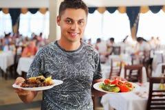 Junger Mann mit zwei Tellern in den Händen an der Gaststätte Stockbild