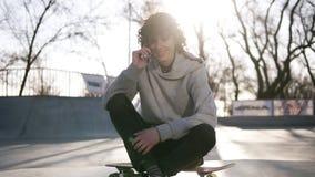 Junger Mann nennt zu den Freunden, die Handy beim Sitzen in einer Rochenzone im Rochenpark verwenden Ein Kerl sitzt auf seinem stock video footage