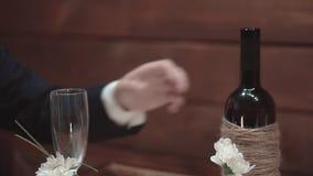 Junger Mann nimmt eine Flasche Wein von einer Tabelle in einem Restaurant, Nahaufnahme, Zeitlupe stock video footage