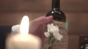 Junger Mann nimmt eine Flasche Wein von einer Tabelle und sitzt in einem Restaurant, Nahaufnahme, Zeitlupe stock video footage