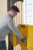 Junger Mann nimmt eine freie Publikation stockfoto