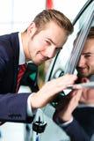 Junger Mann oder Autohändler im Auto-Vertragshändler Lizenzfreie Stockfotos