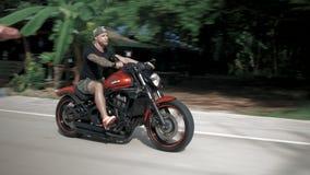 Junger Mann ohne den Sturzhelm, der sein orange Motorrad auf eine Landstraße, Stabilisator reitet stock video
