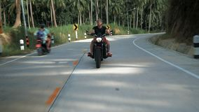Junger Mann ohne den Sturzhelm, der sein orange Motorrad, stabilisierten Schuss reitet stock video