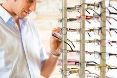Junger Mann am Optiker mit Gläsern Lizenzfreies Stockbild