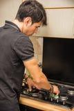 Junger Mann-Reinigungs-Herdplatte mit Schwamm Stockfotos