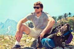Junger Mann-Reisender mit dem Rucksack, der auf felsiger Klippe des Gebirgsgipfels mit Vogelperspektive von Meer sich entspannt Lizenzfreie Stockfotografie