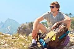 Junger Mann-Reisender mit dem Rucksack, der auf felsiger Klippe des Gebirgsgipfels mit Vogelperspektive von Meer sich entspannt Stockfoto