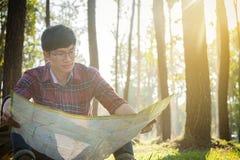 Junger Mann-Reisender mit Rucksack, Betrachtenkarte entspannendes O im Freien Stockbild