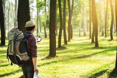 Junger Mann-Reisender mit Rucksack, Betrachtenkarte im digitalen Mobile Lizenzfreies Stockfoto