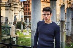 Junger Mann in Rom, das vor Foro Traiano und Fori Imperiali steht Stockfotografie