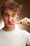 Junger Mann säubert Zähne Stockbild