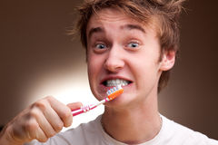 Junger Mann säubert Zähne Stockfoto