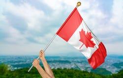 Junger Mann ` s übergibt die Kanada-Staatsflagge im Himmel, Wiedergabe des Teils 3D stolz wellenartig bewegen lizenzfreies stockbild