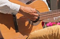 Junger Mann ` s Hand, die eine Gitarre in Madrid, Spanien klimpert stockfotos
