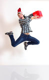 Junger Mann in Sankt-Schutzkappe, die mit Geschenken springt Lizenzfreies Stockfoto