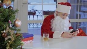 Junger Mann in Santa Claus-Kostüm sitzen auf dem Tisch und schreiben Mitteilung an seinem Telefon stock video